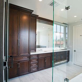 Cette image montre une salle de bain principale design de taille moyenne avec un placard avec porte à panneau encastré, des portes de placard en bois sombre, une douche d'angle, un mur blanc, un sol en bois peint, un lavabo encastré et un plan de toilette en quartz.