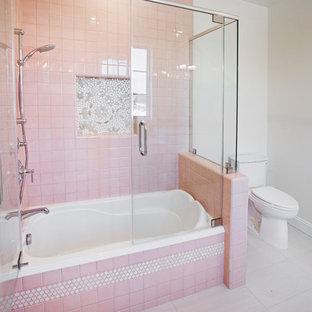 Modelo de cuarto de baño actual, pequeño, con combinación de ducha y bañera, sanitario de una pieza, baldosas y/o azulejos rosa, baldosas y/o azulejos de porcelana, paredes blancas y suelo de baldosas de cerámica