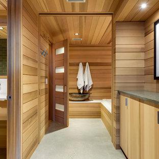 Modelo de sauna rústica con armarios con paneles lisos, puertas de armario de madera clara, lavabo bajoencimera, suelo gris, encimeras blancas y suelo de cemento