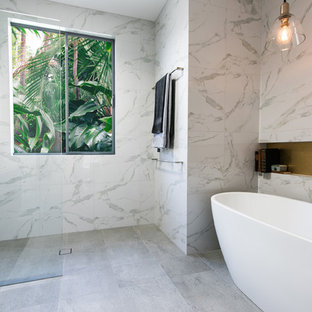 Tropical bathroom in Melbourne with a freestanding tub and an open shower.