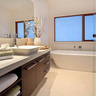 Tropical bathroom in Melbourne with a curbless shower, a freestanding tub and a vessel sink.
