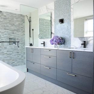 Immagine di una stanza da bagno padronale contemporanea di medie dimensioni con ante lisce, ante in legno bruno, vasca freestanding, doccia alcova, piastrelle blu, lastra di vetro, top in marmo, WC sospeso, pareti beige, pavimento in marmo e lavabo sottopiano