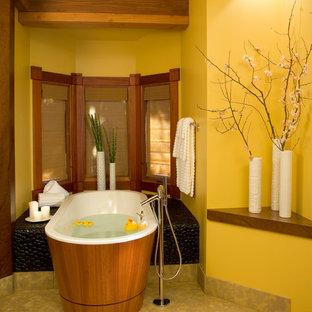 サンディエゴのアジアンスタイルのおしゃれな浴室 (置き型浴槽、黄色い壁、ベージュの床) の写真