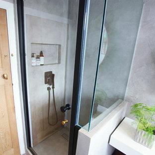 Modelo de cuarto de baño con ducha, moderno, pequeño, con armarios tipo mueble, puertas de armario marrones, ducha abierta, sanitario de pared, baldosas y/o azulejos grises, baldosas y/o azulejos de cemento, paredes grises, suelo de cemento, lavabo con pedestal, encimera de terrazo, suelo gris, ducha con puerta con bisagras y encimeras blancas