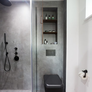 Inredning av ett industriellt litet en-suite badrum, med luckor med profilerade fronter, bruna skåp, en öppen dusch, en vägghängd toalettstol, grå kakel, grå väggar, betonggolv, ett väggmonterat handfat, grått golv och dusch med gångjärnsdörr
