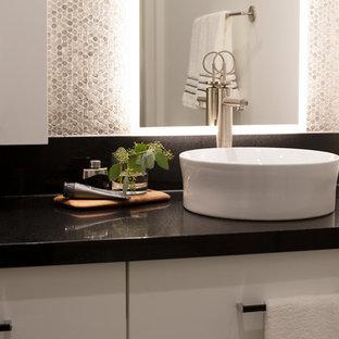 Imagen de cuarto de baño con ducha, moderno, de tamaño medio, con armarios con paneles lisos, puertas de armario blancas, suelo de baldosas tipo guijarro, paredes beige, suelo de baldosas de porcelana, lavabo sobreencimera, encimera de cuarzo compacto, suelo gris y encimeras negras