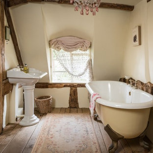 This is an example of a medium sized rustic family bathroom in Other with a claw-foot bath, white walls, medium hardwood flooring, a pedestal sink and beige floors.
