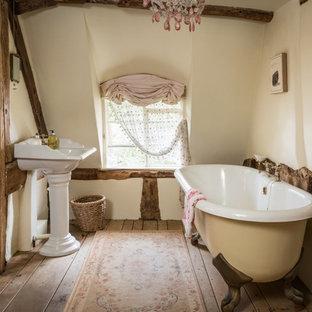 Foto de cuarto de baño infantil, rústico, de tamaño medio, con bañera con patas, paredes blancas, suelo de madera en tonos medios, lavabo con pedestal y suelo beige