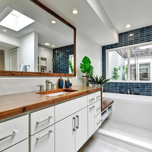 Trendy master blue tile and ceramic tile ceramic floor bathroom photo in Austin with flat-panel cabinets, white cabinets, white walls, an undermount sink and wood countertops