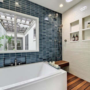 Ispirazione per una stanza da bagno padronale etnica di medie dimensioni con ante lisce, ante bianche, vasca da incasso, doccia aperta, piastrelle blu, piastrelle in ceramica, pareti blu, pavimento in legno massello medio e top in legno