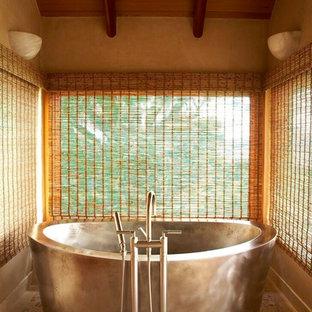 Immagine di una stanza da bagno tropicale con vasca freestanding e piastrelle in pietra