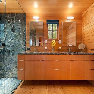 ポートランド(メイン)の小さいモダンスタイルのおしゃれなマスターバスルーム (アンダーカウンター洗面器、フラットパネル扉のキャビネット、中間色木目調キャビネット、御影石の洗面台、ダブルシャワー、分離型トイレ、青いタイル、石スラブタイル、無垢フローリング) の写真