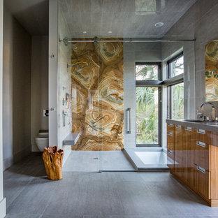Modern inredning av ett stort grå grått en-suite badrum, med släta luckor, skåp i mellenmörkt trä, ett undermonterat badkar, en dusch i en alkov, en vägghängd toalettstol, brun kakel, stenhäll, grå väggar, grått golv och dusch med skjutdörr