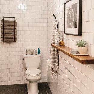 Bild på ett mellanstort funkis en-suite badrum, med en toalettstol med hel cisternkåpa, vit kakel, keramikplattor, vita väggar, marmorgolv och svart golv