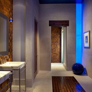 Immagine di una stanza da bagno design con lavabo a consolle e piastrelle effetto legno