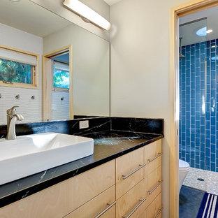 Ejemplo de cuarto de baño contemporáneo con lavabo sobreencimera, puertas de armario de madera clara, encimera de esteatita, ducha a ras de suelo, baldosas y/o azulejos azules, baldosas y/o azulejos de cerámica, paredes blancas, suelo de cemento y armarios con paneles lisos