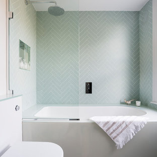 This is an example of a contemporary bathroom in London with an alcove bath, a shower/bath combination, a one-piece toilet, green tiles, grey tiles, green walls and grey floors.