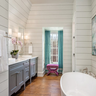 Example of a transitional dark wood floor, brown floor, double-sink and shiplap wall freestanding bathtub design in Other with shaker cabinets, gray cabinets, white walls, a vessel sink, white countertops and a built-in vanity