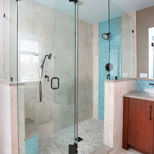 Mid-sized trendy master gray tile pebble tile floor corner shower photo in Chicago with flat-panel cabinets, medium tone wood cabinets, engineered quartz countertops and gray walls