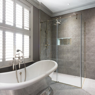 Traditional ensuite bathroom in Kent with a freestanding bath, a built-in shower, grey tiles, grey walls, grey floors and a sliding door.