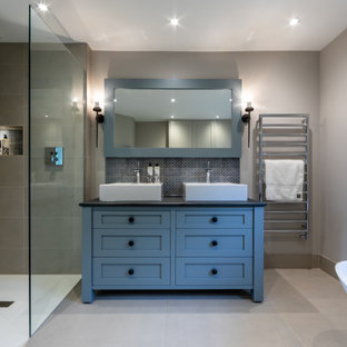 Medium sized classic ensuite bathroom in Surrey with shaker cabinets, blue cabinets, a freestanding bath, a corner shower, grey tiles, porcelain tiles, grey walls, porcelain flooring, a vessel sink, grey floors, black worktops, double sinks, a wall niche and a freestanding vanity unit.