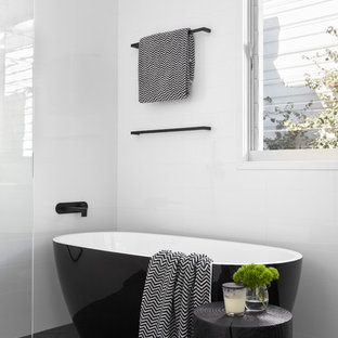 This is an example of a mid-sized contemporary master bathroom in Melbourne with a freestanding tub, an open shower, white walls, beaded inset cabinets, light wood cabinets, multi-coloured tile, mosaic tile, a drop-in sink and solid surface benchtops.