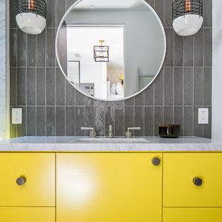 オレンジカウンティのコンテンポラリースタイルのおしゃれなバスルーム (浴槽なし) (フラットパネル扉のキャビネット、黄色いキャビネット、グレーのタイル、ガラスタイル、グレーの壁、無垢フローリング、アンダーカウンター洗面器、茶色い床、白い洗面カウンター) の写真