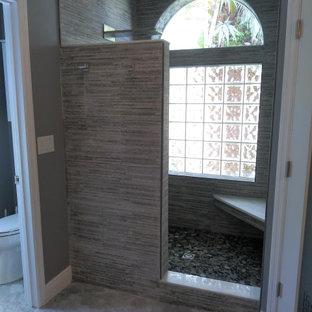 オーランドの中くらいのおしゃれなマスターバスルーム (シェーカースタイル扉のキャビネット、グレーのキャビネット、オープン型シャワー、分離型トイレ、グレーのタイル、磁器タイル、グレーの壁、クッションフロア、ベッセル式洗面器、クオーツストーンの洗面台、グレーの床、オープンシャワー、白い洗面カウンター、シャワーベンチ、洗面台2つ、造り付け洗面台) の写真