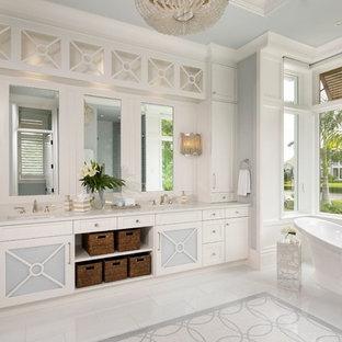Immagine di una stanza da bagno padronale tropicale con ante con riquadro incassato, ante bianche, vasca freestanding, lavabo sottopiano, pavimento multicolore e top bianco