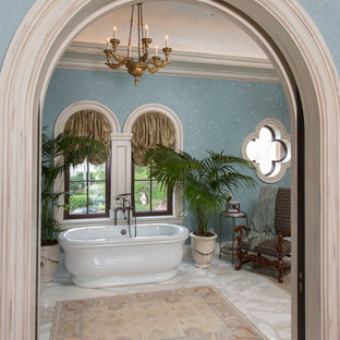 Large mediterranean ensuite bathroom in Miami with a freestanding bath, blue walls, marble flooring and white floors.