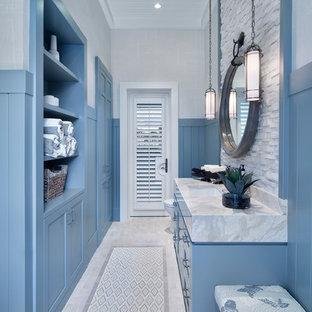 Imagen de cuarto de baño costero con armarios abiertos, puertas de armario azules, paredes azules y lavabo bajoencimera