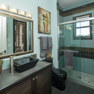 Trendy gray floor alcove shower photo in Miami with louvered cabinets, dark wood cabinets, blue walls, a vessel sink, tile countertops and gray countertops