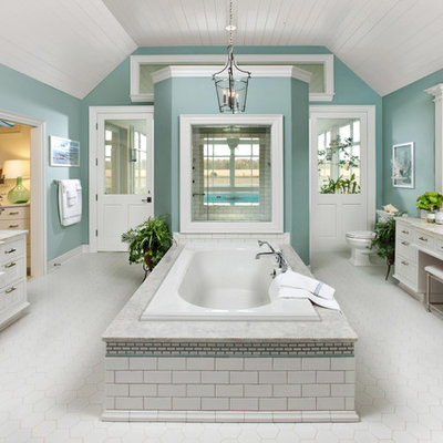 Example of a large classic master white tile and ceramic tile ceramic tile drop-in bathtub design in Milwaukee with a drop-in sink, flat-panel cabinets, white cabinets, granite countertops, a one-piece toilet, green walls and beige countertops