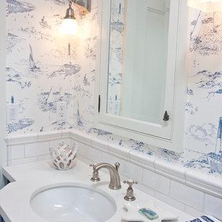 Esempio di una stanza da bagno con doccia costiera di medie dimensioni con lavabo sottopiano, ante blu, piastrelle bianche, pareti multicolore, top in superficie solida, ante lisce e piastrelle diamantate