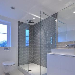 ロンドンの中サイズのコンテンポラリースタイルのおしゃれな浴室 (ベッセル式洗面器、フラットパネル扉のキャビネット、白いキャビネット、コーナー設置型シャワー、壁掛け式トイレ、グレーのタイル、サブウェイタイル、白い壁) の写真