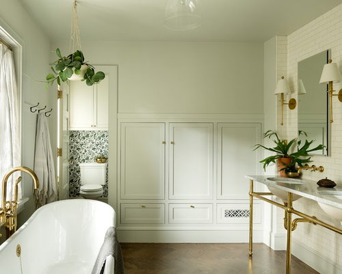 mid sized transitional master bathroom idea in portland with a freestanding tub white tile