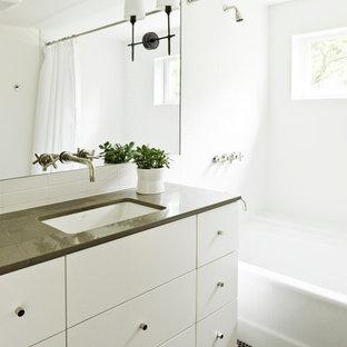 Идея дизайна: ванная комната в современном стиле с врезной раковиной, плоскими фасадами, белыми фасадами, ванной в нише, душем над ванной и черным полом