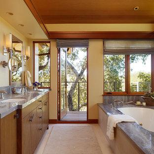 Foto di un'ampia stanza da bagno padronale minimal con ante lisce, ante in legno bruno, vasca sottopiano, top in pietra calcarea, pareti beige, pavimento in gres porcellanato e lavabo sottopiano