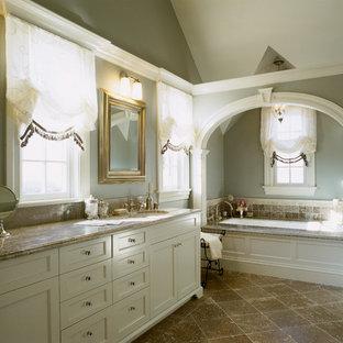 Imagen de cuarto de baño principal, de estilo americano, grande, con armarios con paneles empotrados, puertas de armario blancas, bañera empotrada, baldosas y/o azulejos beige, baldosas y/o azulejos de piedra, paredes azules, suelo de travertino, lavabo bajoencimera y encimera de granito