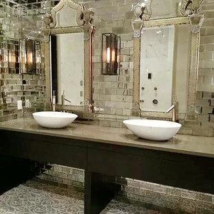 Imagen de cuarto de baño principal, bohemio, grande, con lavabo sobreencimera, armarios con paneles lisos, puertas de armario de madera en tonos medios, encimera de acrílico, ducha doble, baldosas y/o azulejos grises, baldosas y/o azulejos con efecto espejo, paredes grises y suelo de mármol