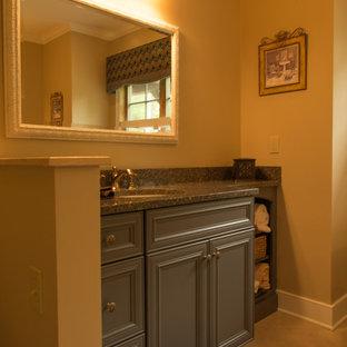 Idee per una stanza da bagno classica con lavabo a bacinella, ante con bugna sagomata, ante verdi, top in granito, WC monopezzo, piastrelle grigie, lastra di pietra, pareti beige e pavimento in marmo