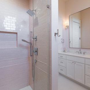 Foto de cuarto de baño con ducha, romántico, de tamaño medio, con armarios estilo shaker, puertas de armario blancas, ducha empotrada, baldosas y/o azulejos grises, baldosas y/o azulejos de cemento, paredes rosas, suelo de baldosas de porcelana, lavabo bajoencimera, encimera de cuarzo compacto, suelo blanco y ducha con puerta con bisagras