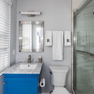 Ispirazione per una piccola stanza da bagno con doccia stile shabby con ante con riquadro incassato, ante blu, doccia alcova, WC a due pezzi, piastrelle in gres porcellanato, pareti grigie, lavabo sottopiano, top in marmo, porta doccia scorrevole e top grigio