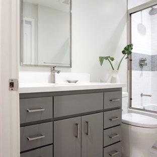 サンフランシスコの中くらいのコンテンポラリースタイルのおしゃれな浴室 (フラットパネル扉のキャビネット、グレーのキャビネット、アルコーブ型浴槽、シャワー付き浴槽、一体型トイレ、白いタイル、サブウェイタイル、白い壁、木目調タイルの床、アンダーカウンター洗面器、クオーツストーンの洗面台、ベージュの床、引戸のシャワー、白い洗面カウンター、ニッチ、洗面台1つ、造り付け洗面台) の写真