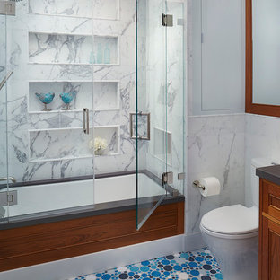 Photo of a transitional bathroom in San Francisco with recessed-panel cabinets, medium wood cabinets, an undermount tub, a shower/bathtub combo, a two-piece toilet, grey walls and mosaic tile floors.