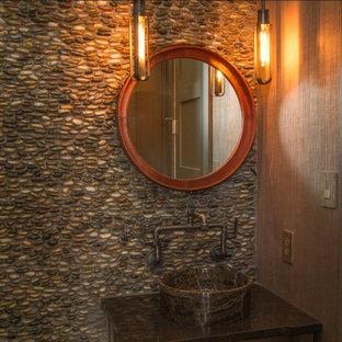 Diseño de cuarto de baño de estilo de casa de campo, pequeño, con armarios estilo shaker, puertas de armario marrones, baldosas y/o azulejos marrones, suelo de baldosas tipo guijarro, paredes marrones, lavabo sobreencimera, encimera de granito y encimeras negras