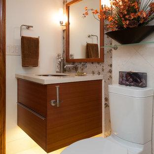 Immagine di una stanza da bagno tropicale con ante lisce, ante in legno scuro, WC a due pezzi, piastrelle bianche, piastrelle di vetro, pareti beige, pavimento in pietra calcarea, lavabo sottopiano e top in quarzo composito