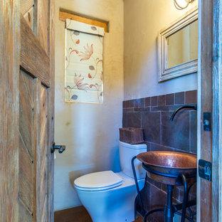 Modelo de cuarto de baño con ducha, de estilo americano, de tamaño medio, con armarios tipo mueble, puertas de armario con efecto envejecido, sanitario de dos piezas, baldosas y/o azulejos multicolor, baldosas y/o azulejos de piedra, paredes beige, suelo de cemento, lavabo con pedestal, encimera de cobre, suelo rojo y encimeras naranjas