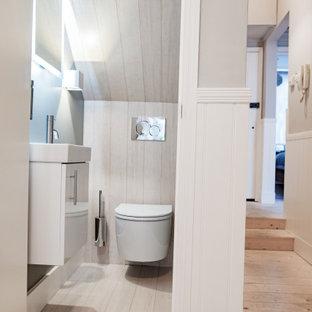 Imagen de cuarto de baño minimalista, pequeño, con armarios con paneles lisos, puertas de armario blancas, sanitario de pared, paredes grises, suelo de bambú y suelo blanco