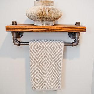 Modelo de cuarto de baño con ducha, rural, pequeño, con armarios abiertos, sanitario de una pieza, paredes grises, suelo de madera oscura, lavabo sobreencimera y encimera de madera